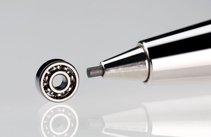 Picture of a miniature bearing in size comparison with a pen