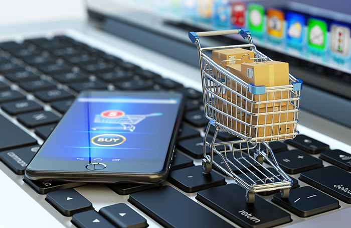 Picture of mobile phone and shopping cart full of package boxes on computer laptop